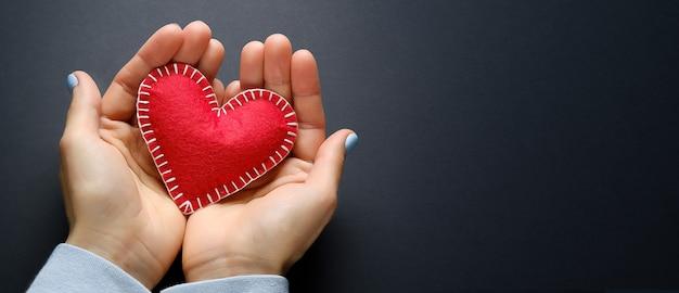Rood hart of valentine in de handen van een meisje, op een zwarte achtergrond. het concept van het vieren van valentijnsdag. symbool van de liefde. banner.