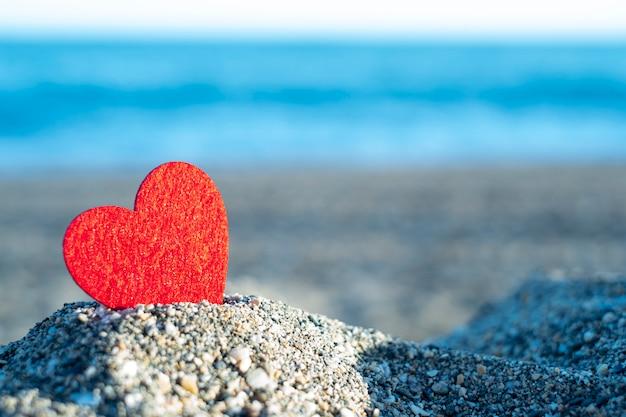 Rood hart op een berg zand aan zee. concept van san valentine