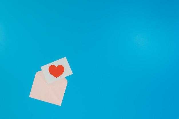 Rood hart op een witte kaart met een roze envelop op een blauwe achtergrond