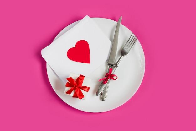 Rood hart op een witte plaat, een vork, een mes, een geschenkdoos, liefdesbrief op roze