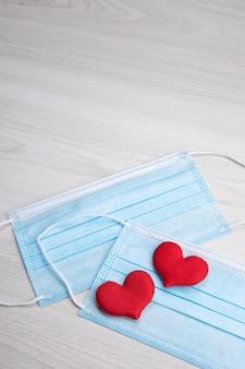 Rood hart op medische gezichtsmaskers. conceptondersteuning, liefde, zorg en een bedankje aan de eerstelijns essentiële werkers en gezondheidszorg. gelukkige valentijnsdag. pandemie, coronavirus in quarantaine. valentijnsdag.