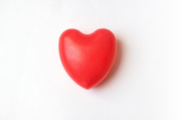 Rood hart op witte achtergrond. liefde, zorg en valentine day concept. wereldhartgezondheidsdag idee.