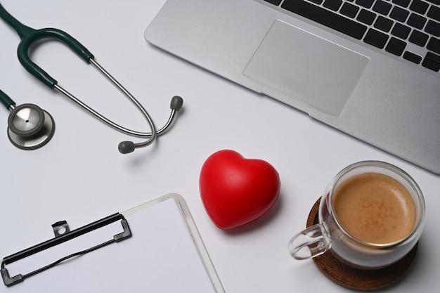 Rood hart, stethoscoop en klembord op witte tafel. cardiologie en verzekeringsconcept.