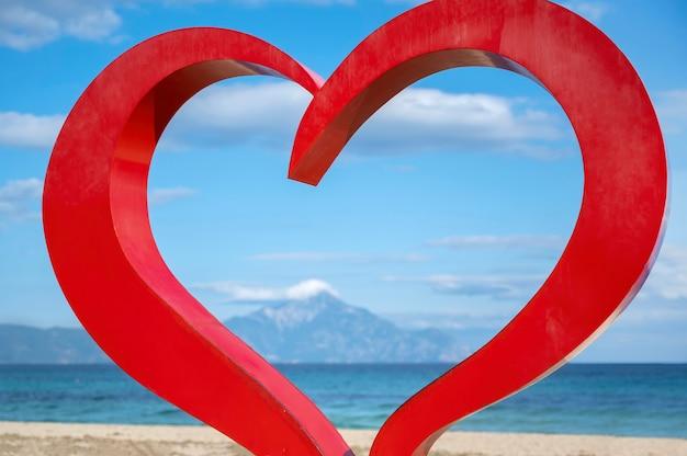 Rood hart teken op de egeïsche zeekust met water en bergen, in sarti, griekenland