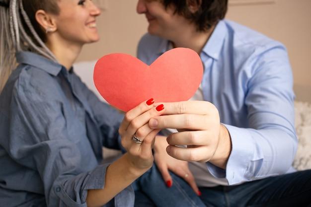 Rood hart valentijn. mooie jonge paar in slaapkamer zittend op bed en knuffelen.