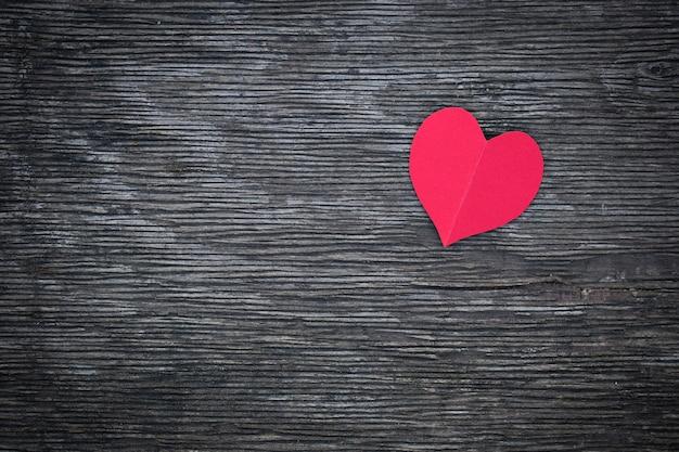 Rood hart van een papier ligt op een oud bord