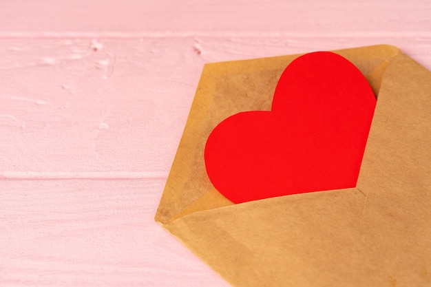 Rood hartdecoratie in envelop op roze houten lijst
