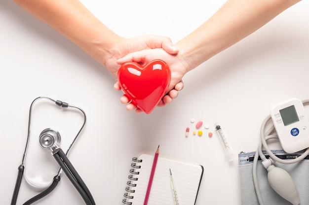 Rood hartmodel op een paarhanden holding