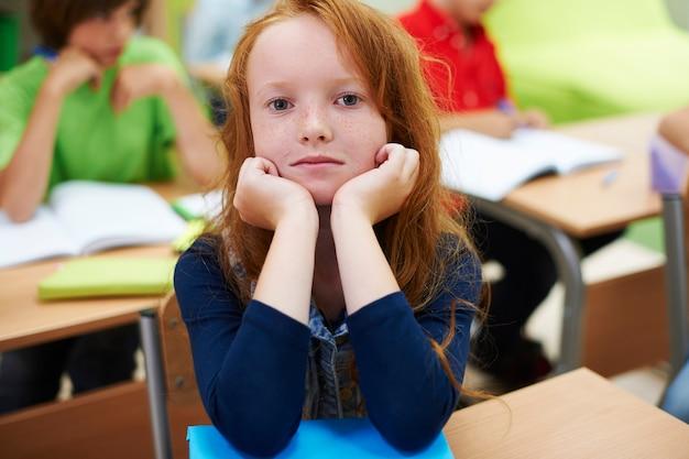 Rood hoofd meisje in de klas