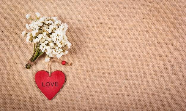 Rood houten hart en boeket van witte wilde bloemen.