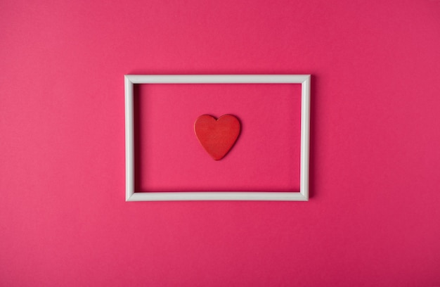 Rood houten hart in het witte fotolijstje. valentijnsdag concept. plat lag, bovenaanzicht.