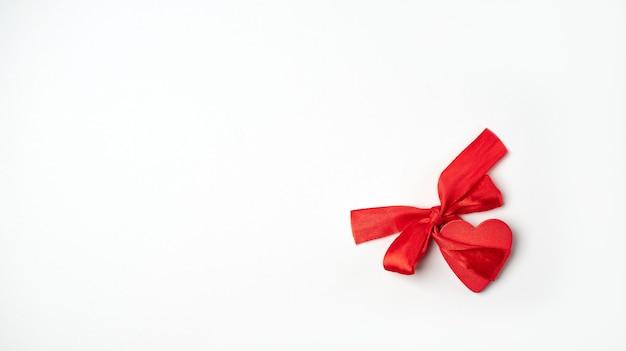 Rood houten hart met rode boog-knoop op de lichte (witte) achtergrond. valentijnsdag concept