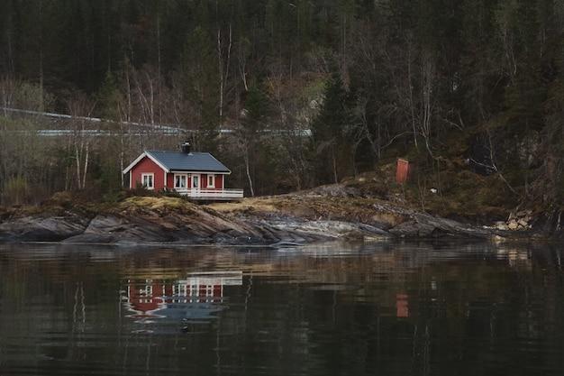 Rood houten huis in de buurt van het meer tegen de achtergrond van het bos en de bergen