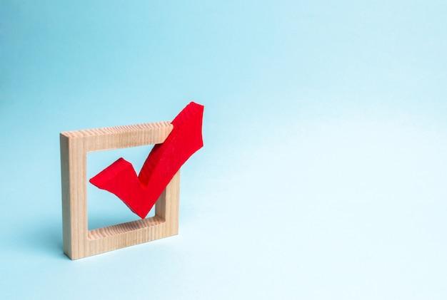 Rood houten vinkje voor stemming over verkiezingen op een blauwe achtergrond.