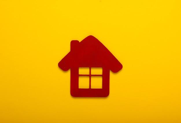 Rood huisbeeldje op gele achtergrond. bovenaanzicht