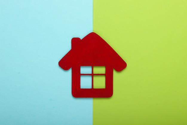 Rood huisbeeldje op groenachtig blauwe achtergrond. bovenaanzicht