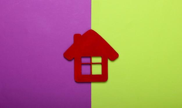 Rood huisbeeldje op purpere groene achtergrond. bovenaanzicht