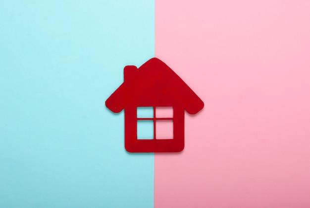 Rood huisbeeldje op roze-blauwe pastelkleurachtergrond. bovenaanzicht