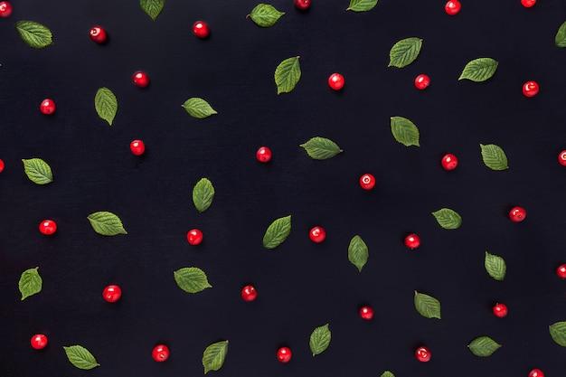 Rood kersenpatroon met groene bladeren op zwarte houten achtergrond