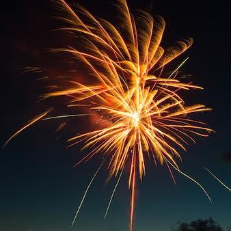 Rood kleurrijk vuurwerk op blauwe hemelachtergrond
