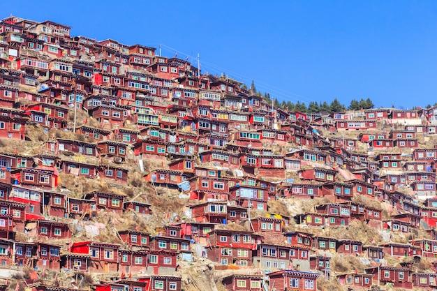 Rood klooster bij larung-gar (boeddhistische academie) in zonneschijndag