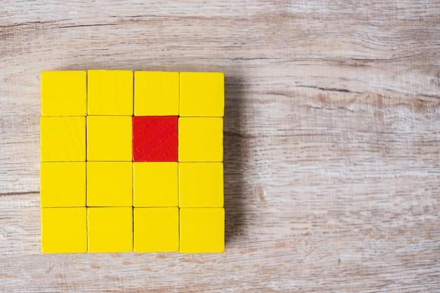Rood kubusblok verschillend van menigte van gele blokken