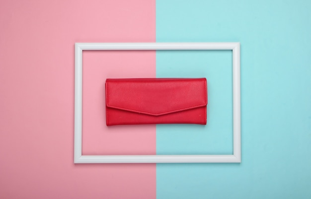 Rood lederen portemonnee in een wit frame op roze blauwe ondergrond