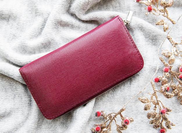Rood lederen portemonnee op grijs gebreid oppervlak
