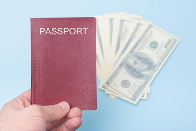 Rood leeg paspoort in de hand van de man. dollar. blauwe achtergrond
