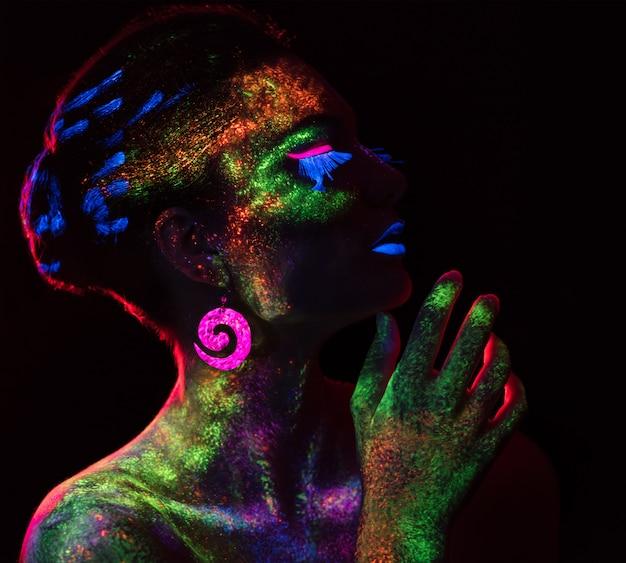 Rood lichtcontour op de sensuele vrouw met fluorescerende verfmake-up