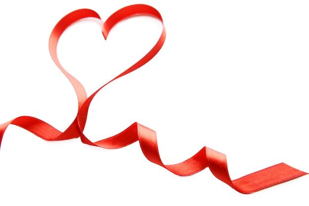 Rood lint in de vorm van een hart dat op wit wordt geïsoleerd