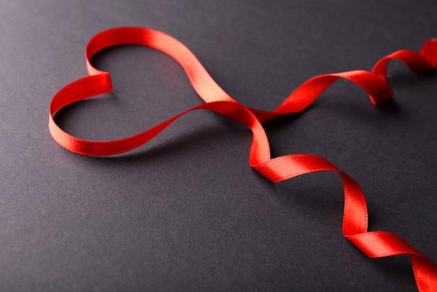 Rood lint in de vorm van een hart op een grijze achtergrond