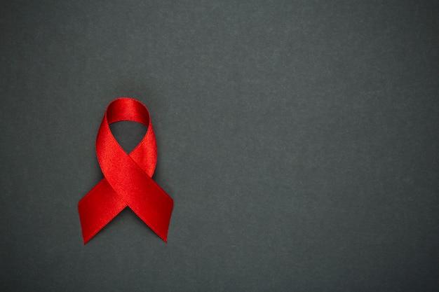 Rood lint op een donkergrijze achtergrond. symbool van de wereld aidsdag of kanker of hiv awareness month en concept van de gezondheidszorg. kopieer ruimte