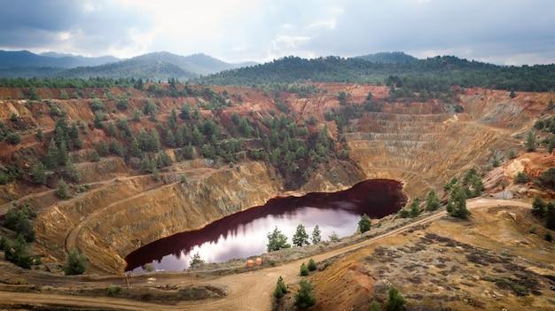 Rood meer in krater van verlaten kokkinopezoula open-pit kopermijn in de buurt van mitsero, cyprus. de vreemde kleur is afkomstig van hoge niveaus van zuren en zware metalen