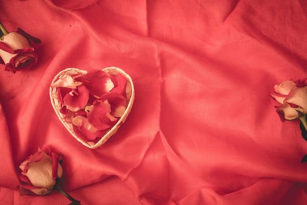 Rood nam bloemblaadje op de achtergrond van de hartvorm copyspace toe