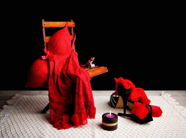 Rood ondergoed op stoel naast kaars