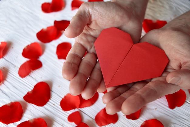 Rood origamidocument hart in mannelijke handen en rozenblaadjes. valentijnsdag concept