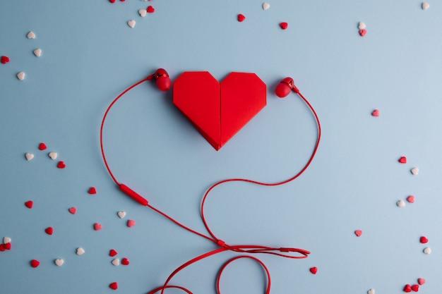 Rood origamihart met hoofdtelefoons op blauwe lijst