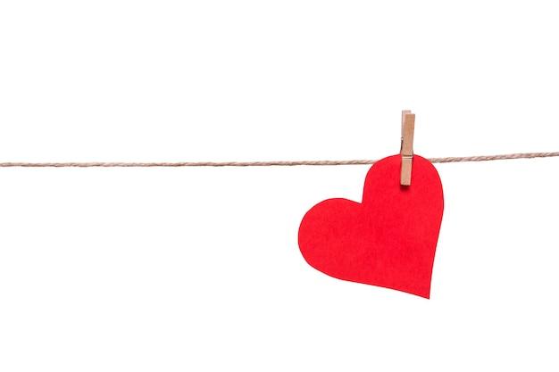 Rood papier hart en wasknijper op een touw geïsoleerd op een witte achtergrond.