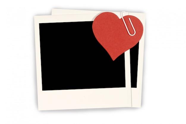 Rood papieren hart bevestigd aan lege polaroid-fotoafdrukken