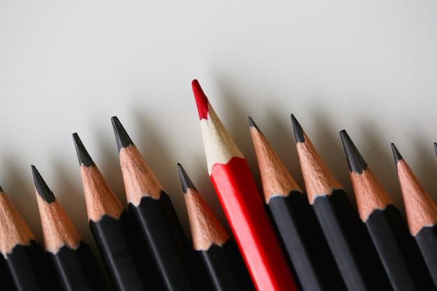Rood potlood dat van menigte van overvloed duidelijk uitkomt