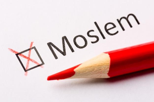 Rood potlood en de inscriptie moslim met kruis op wit papier.