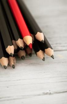 Rood potlood onderscheidt zich van de menigte van zwart potlood op een houten witte achtergrond.