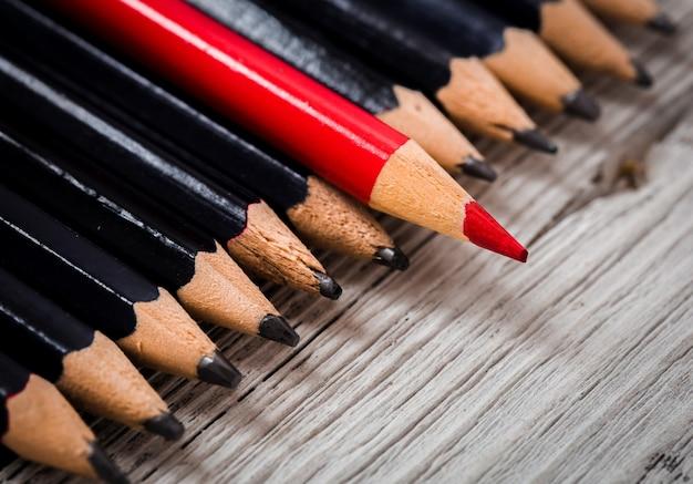 Rood potlood onderscheidt zich van de menigte zwart op een houten witte tafel