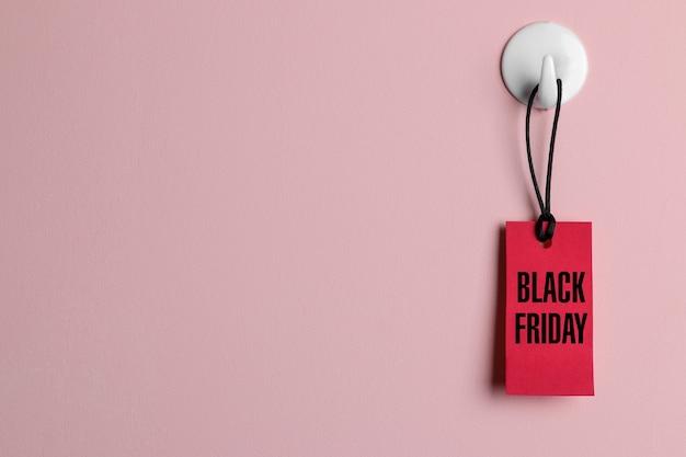 Rood prijskaartje hangend aan een haak aan de muur met het opschrift black friday