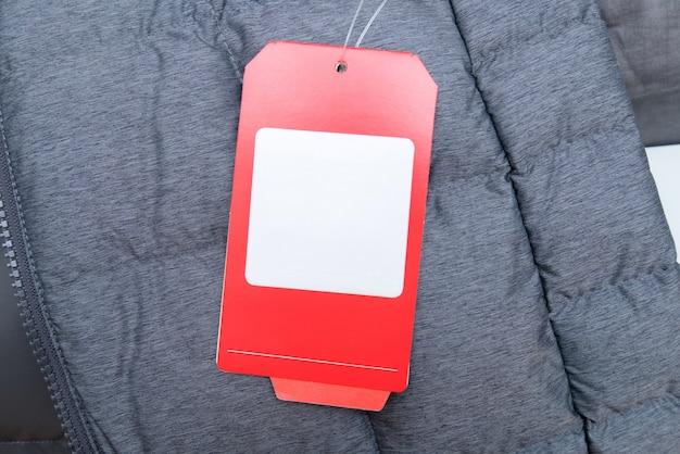 Rood prijskaartje op grijs winterjasje met ruimte voor uw tekst.