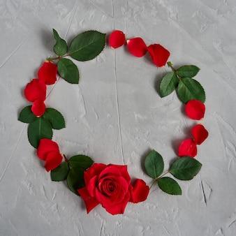 Rood roze bloemen, bloemblaadjes, bladeren cirkelframe geïsoleerd op een grijze gestructureerde achtergrond plat lag, bovenaanzicht