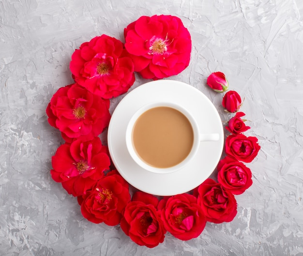 Rood roze bloemen in een spiraal en een kopje koffie op een grijze betonnen achtergrond. bovenaanzicht.