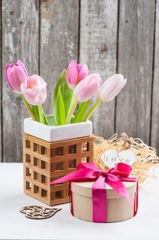 Rood roze gele tulpen en geschenkdoos met rood lint