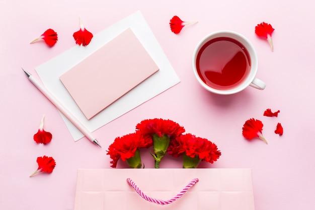 Rood-roze objecten. kopje thee, anjer bloemen kladblok voor tekst op pastel roze achtergrond.